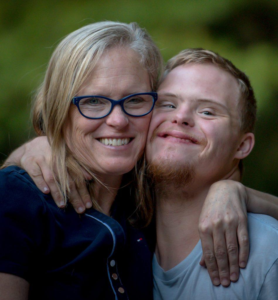 A mother embraces her disabled son